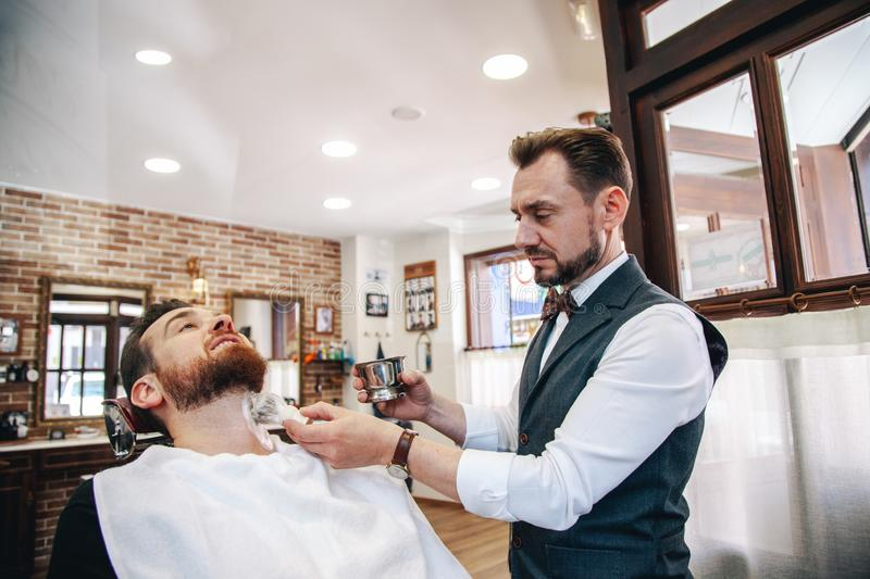 A barber shaves his client`s beard in the traditional way. stock photos
