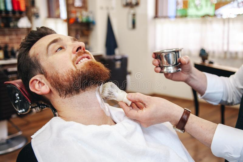 A barber shaves his client`s beard in the traditional way. stock photography