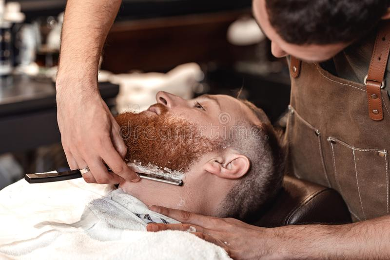 Barber and bearded man in barber shop royalty free stock photos