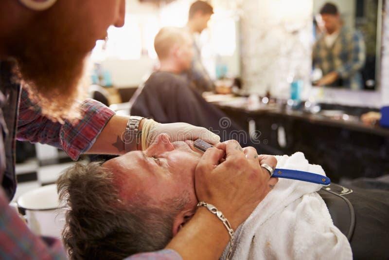 Barber Shaving Client With Cut-Keelscheermes stock afbeeldingen