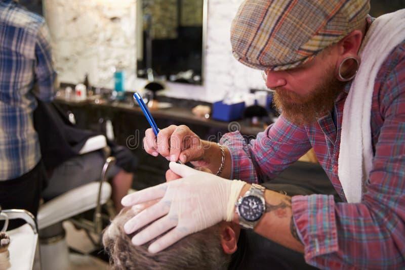 Barber Shaving Client With Cut-Keelscheermes stock afbeelding
