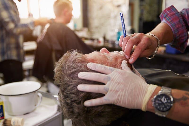 Barber Shaving Client With Cut-Keelscheermes royalty-vrije stock afbeelding