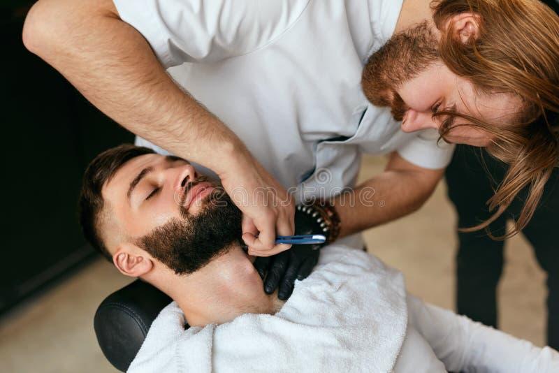 Barber Shaving Man Beard With rak rakkniv i Barber Shop arkivbilder