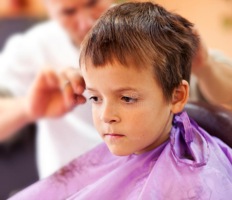 Barber shop blues. Little boy having a haircut in the barber shop - closeup royalty free stock photography