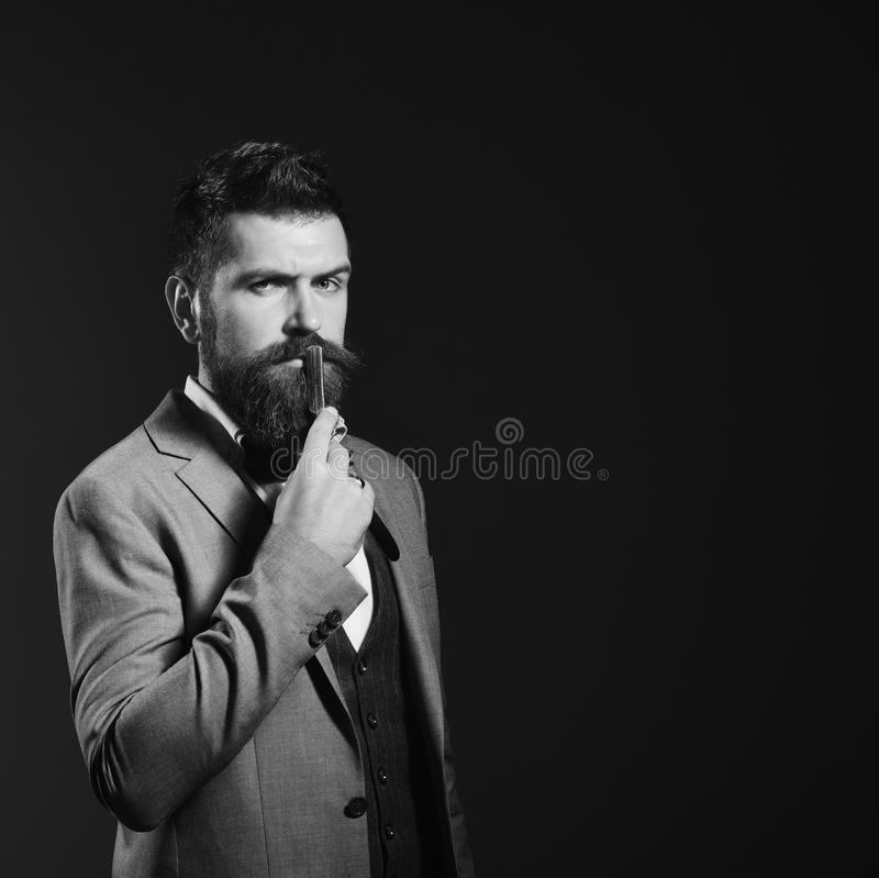 Barber shop. Hair style. Man with long beard holds blade for razor near mouth. Businessman with serious face on dark red background royalty free stock photo