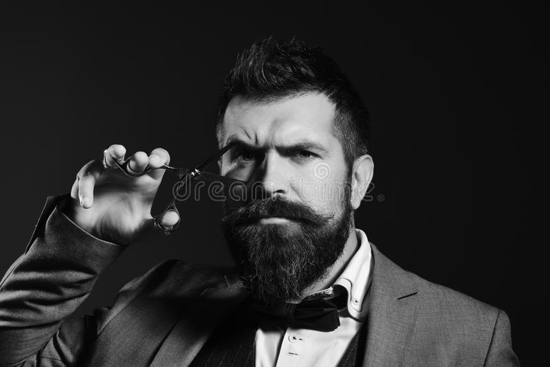 Barber shop. Hair style. Man with long beard holds steel scissors. Macho in formal suit pretends to cut eye. Barbershop advertising concept stock image
