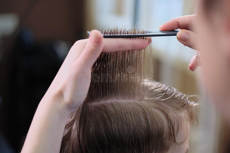 Barber shop. Hairdresser makes hairstyle to a  boy with hair scissors and black comb. royalty free stock photo