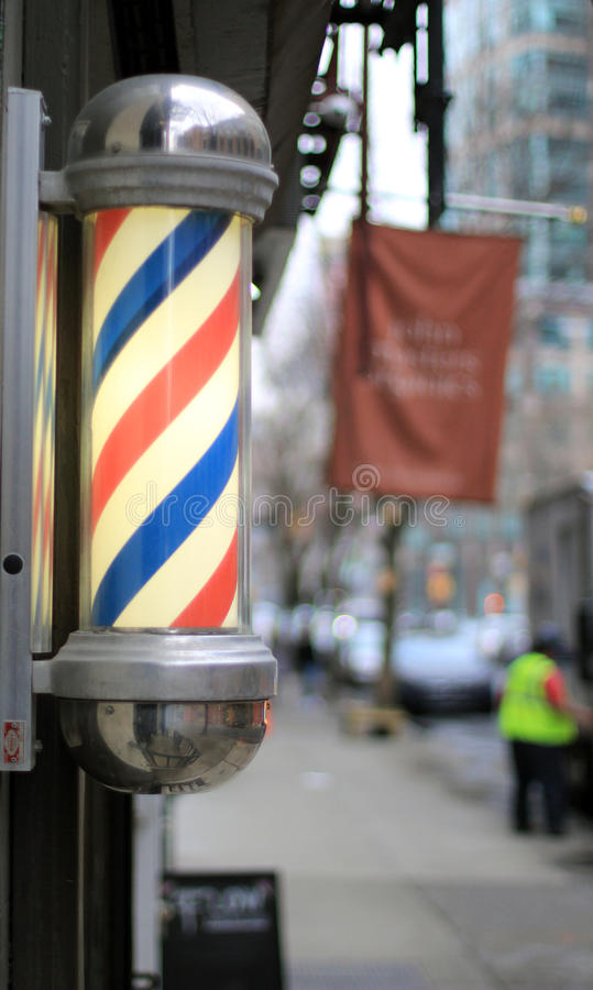 Barber Shop Sign. Barbershop pole with city background royalty free stock images