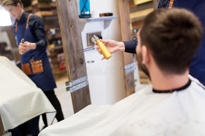 Barber showing hair styling spray to male customer. Grooming, hairdressing and people concept - hairstylist showing hair styling spray to male customer at stock images