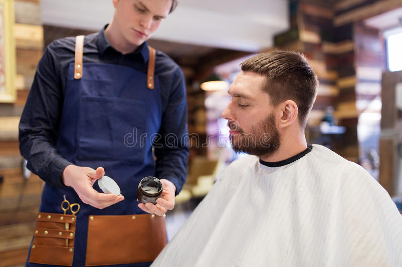 Barber showing hair styling wax to male customer. Grooming, hairdressing and people concept - hairstylist showing hair styling wax to male customer at barbershop stock photo