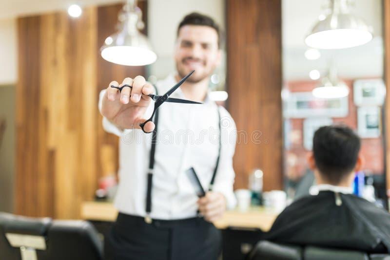 Barber Showing Scissors While Working in Salon royalty-vrije stock afbeeldingen