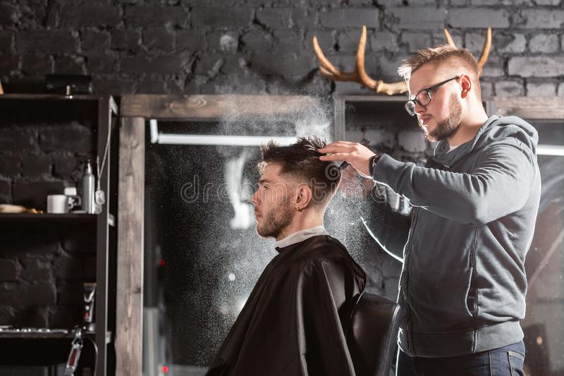 Barber sprays clean water on head in barbershop. Professional trimmer tool cuts beard and hair on young guy in barber. Hair cutting with metal scissors. Master stock photo