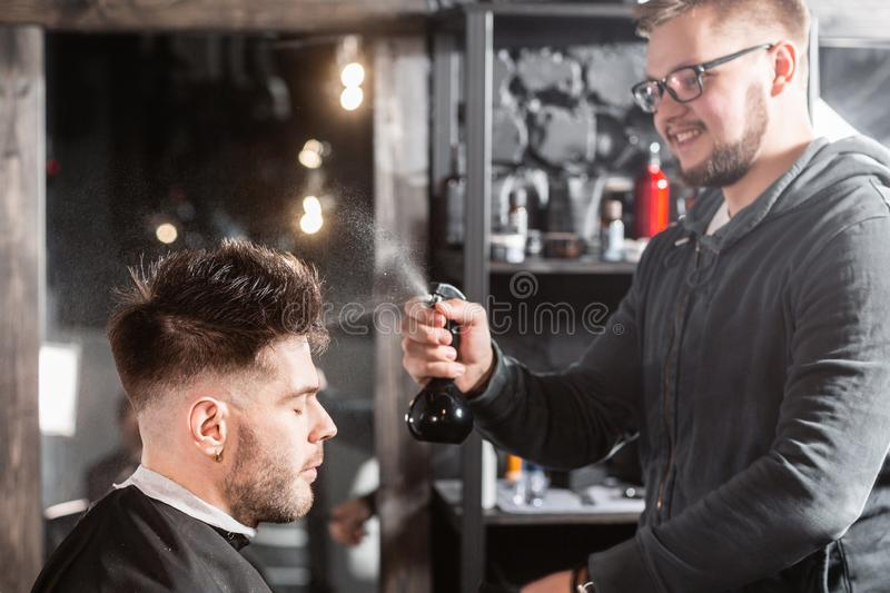 Barber sprays clean water on head in barbershop. Professional trimmer tool cuts beard and hair on young guy in barber stock photo
