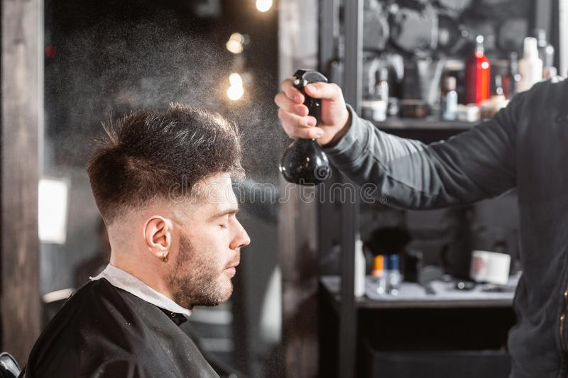 Barber sprays clean water on head in barbershop. Professional trimmer tool cuts beard and hair on young guy in barber stock images