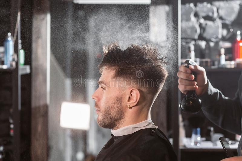 Barber sprays clean water on head in barbershop. Professional trimmer tool cuts beard and hair on young guy in barber royalty free stock image