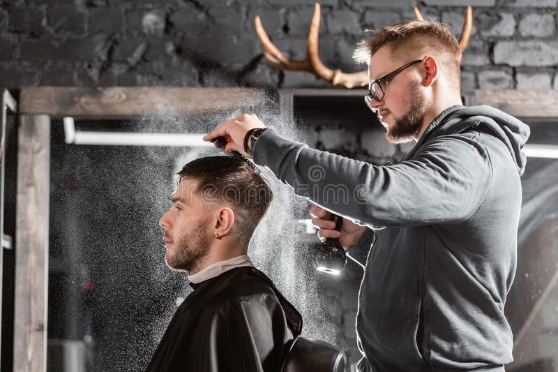Barber sprays clean water on head in barbershop. Professional trimmer tool cuts beard and hair on young guy in barber. Hair cutting with metal scissors. Master royalty free stock images