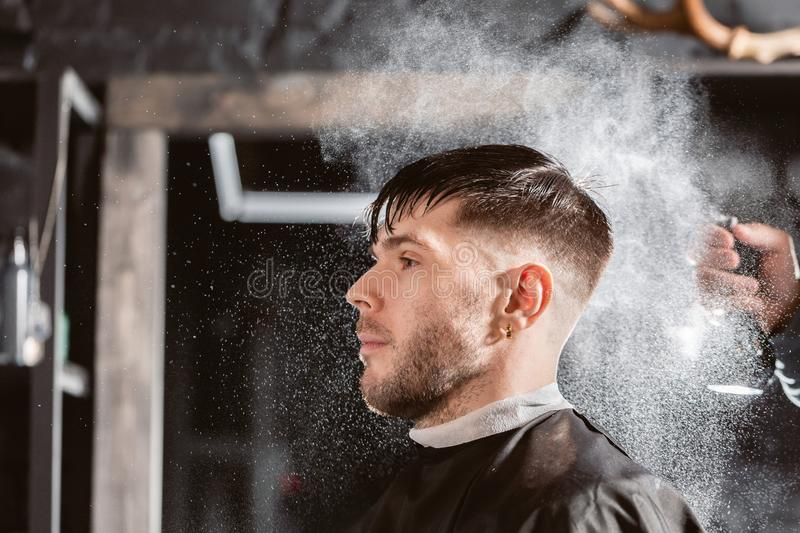 Barber sprays clean water on head in barbershop. Professional trimmer tool cuts beard and hair on young guy in barber. Hair cutting with metal scissors. Master stock photos