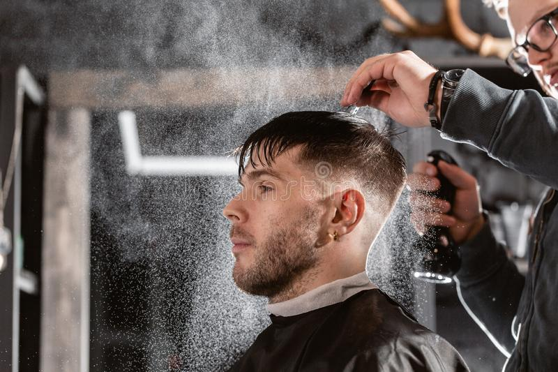 Barber sprays clean water on head in barbershop. Professional trimmer tool cuts beard and hair on young guy in barber. Hair cutting with metal scissors. Master royalty free stock image