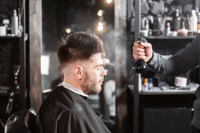 Barber sprays clean water on head in barbershop. Professional trimmer tool cuts beard and hair on young guy in barber. Hair cutting with metal scissors. Master stock image