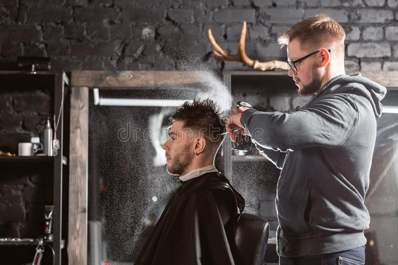 Barber sprays clean water on head in barbershop. Professional trimmer tool cuts beard and hair on young guy in barber royalty free stock photos
