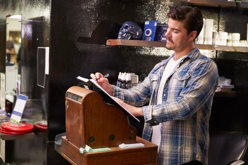 Barber Standing By Cash Register masculina que anota la reservación foto de archivo libre de regalías