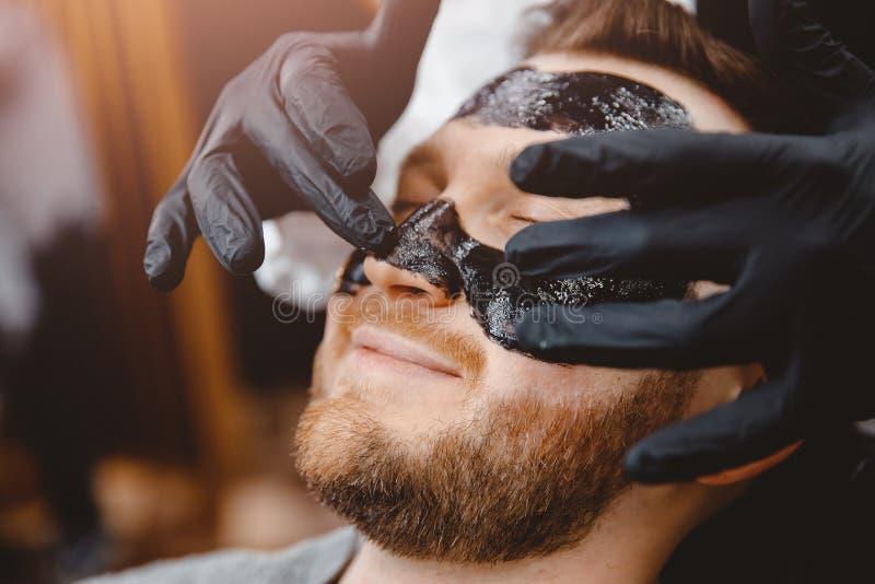 Barber stosuje czarną maskę z węglem drzewnym do czystej skóry porów i usuwa trądzik z nosa, salon spa obrazy stock