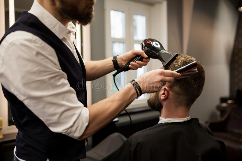 Barber styling customer hair with drier stock photo