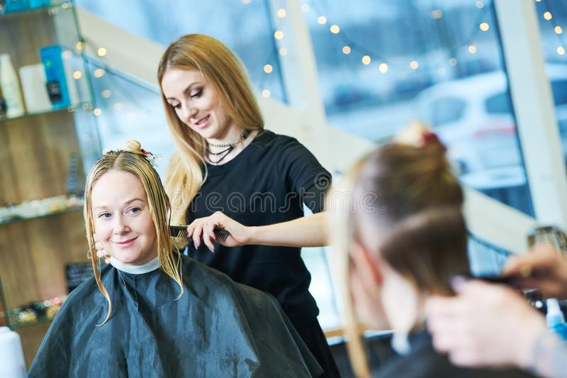 Barber or stylist at work. Hairdresser cutting woman hair royalty free stock photos