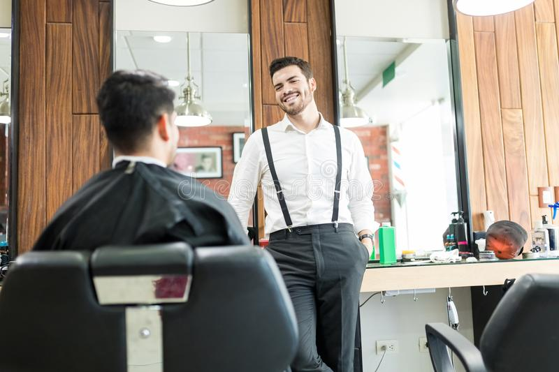 Barber Talking To Customer While que pregunta por sus preferencias foto de archivo