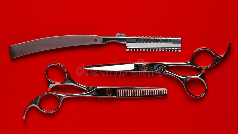 Barber tool on a red background. Scissors for cutting hair top view royalty free stock photography