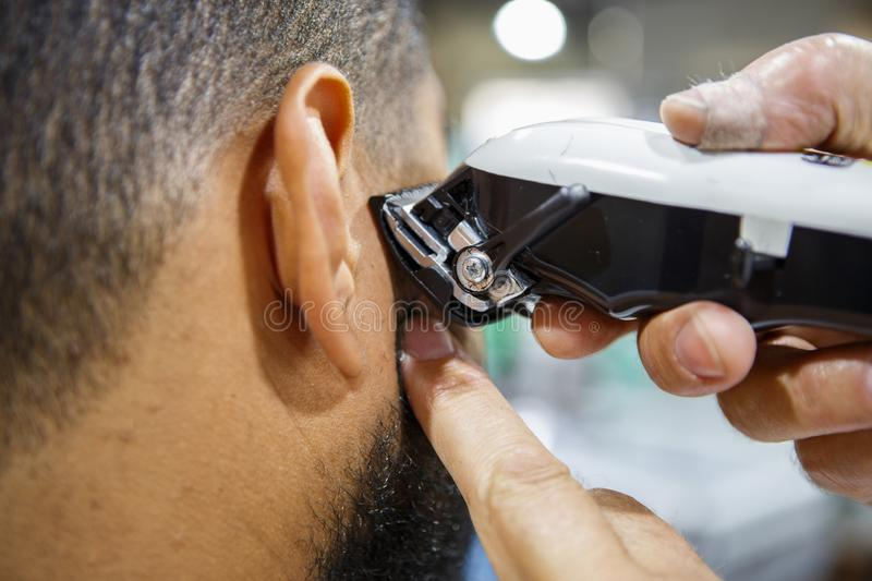 Young black man client get new haircut in barbershop. Barber trim African man client with clipper machine in barbershop.Professional trimmer tool cuts beard and stock photo