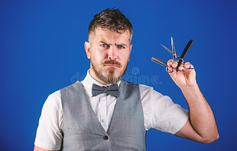 Barber unshaven hipster with sharp straight razor. Barbershop hairdresser salon. Barber beard grooming tips. Man vest. With bow tie hold straight razor blue royalty free stock images