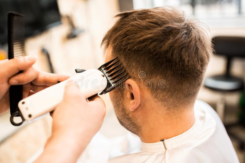 Barber using grooming machine to making haircut to client. Close up stock images