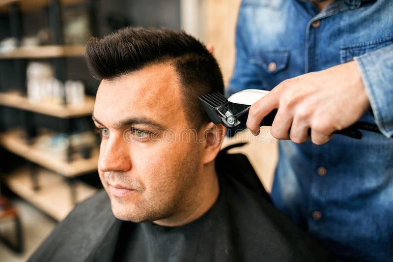 Barber using grooming machine to making haircut to client. Close up royalty free stock photo
