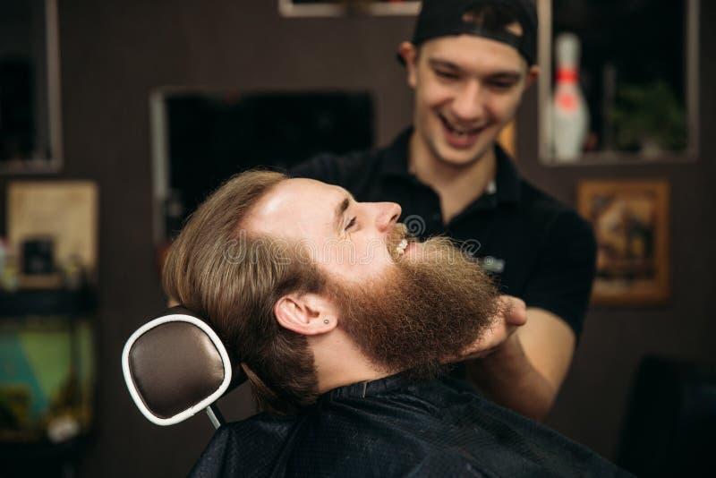 Barber using scissors and comb in barbershop stock image