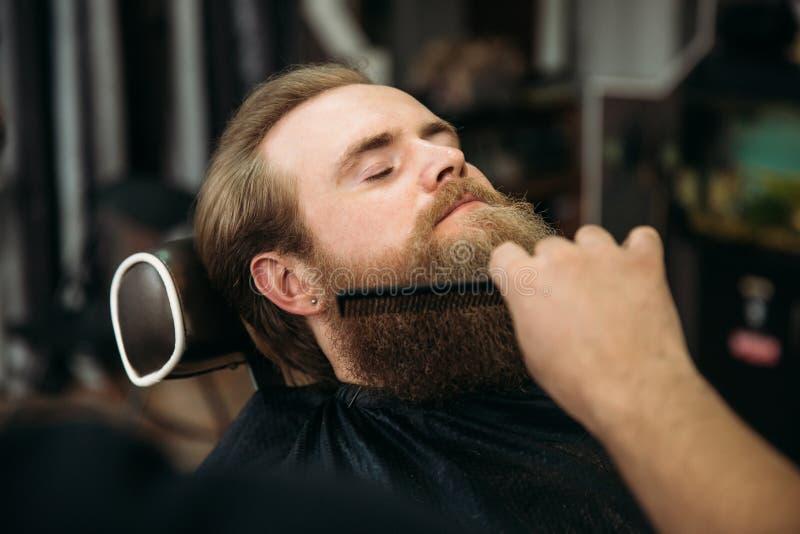 Barber using scissors and comb in barbershop stock photos
