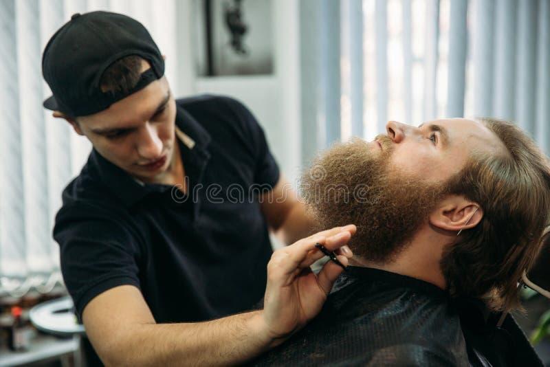 Barber using scissors and comb in barbershop stock photo