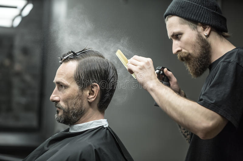 Barber is using spray bottle. Stylish barber with a big beard splashes from the spray bottle at the hair comb next to his client`s head in the barbershop. He stock image