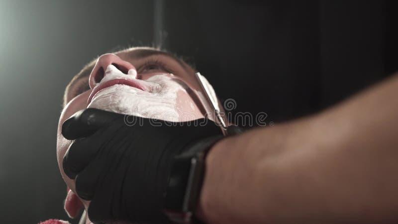 Barber w czarnych rękawiczkach bardzo ostrożnie goli klientów brodą z niebezpieczną brzytwą Czarne tło fotografia royalty free