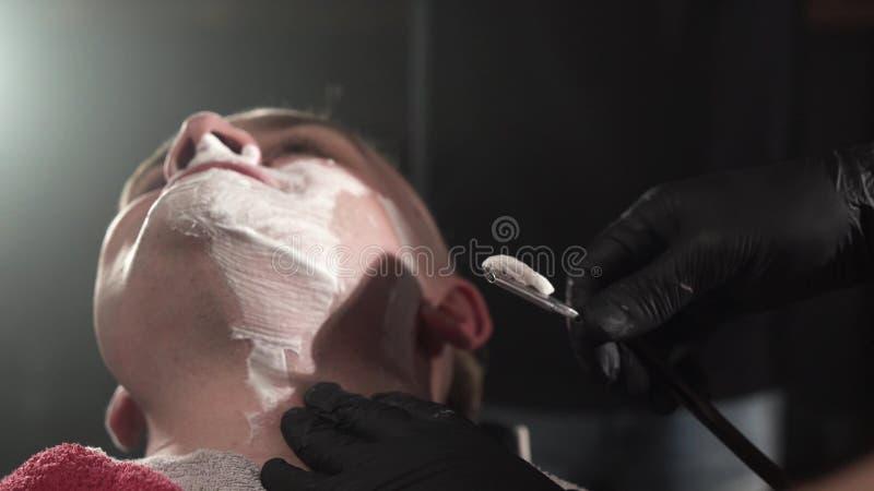 Barber w czarnych rękawiczkach bardzo ostrożnie goli klientów brodą z niebezpieczną brzytwą Czarne tło zdjęcie royalty free