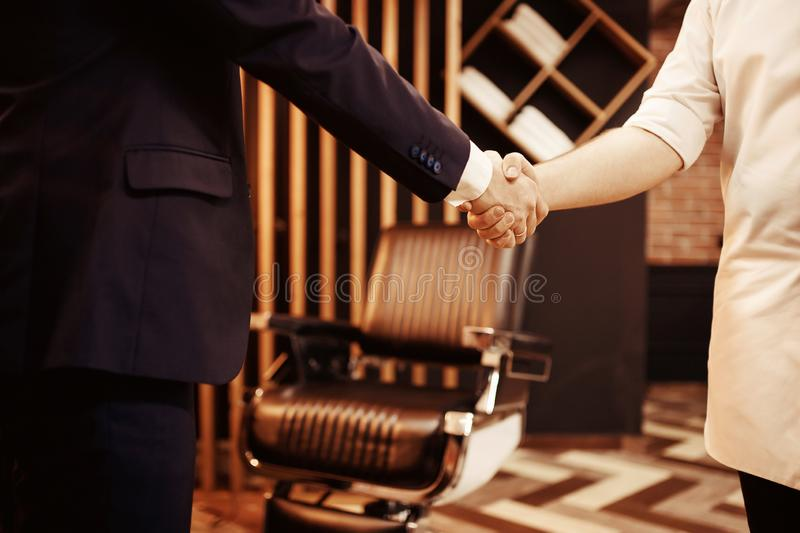 Barber welcomes customer with handshake at Barbershop hairdresser. Concept of trust and care.  stock photography