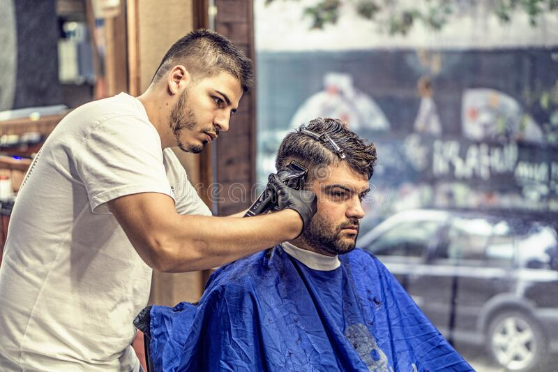 Barber In White Shirt Trimming Man's Hair In Blue Textile While Sitting Nearby Glass Window Free Public Domain Cc0 Image