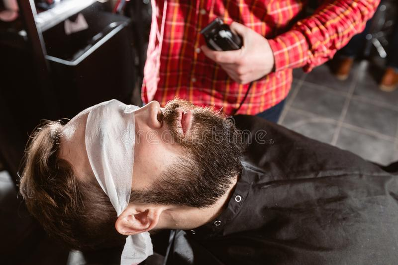 Barber work with clipper machine in barbershop. Professional trimmer tool cuts beard and hair of young guy in barber. Shop salon stock image