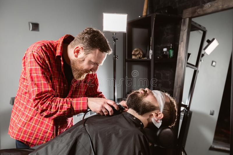 Barber work with clipper machine in barbershop. Professional trimmer tool cuts beard and hair of young guy in barber. Shop salon stock images