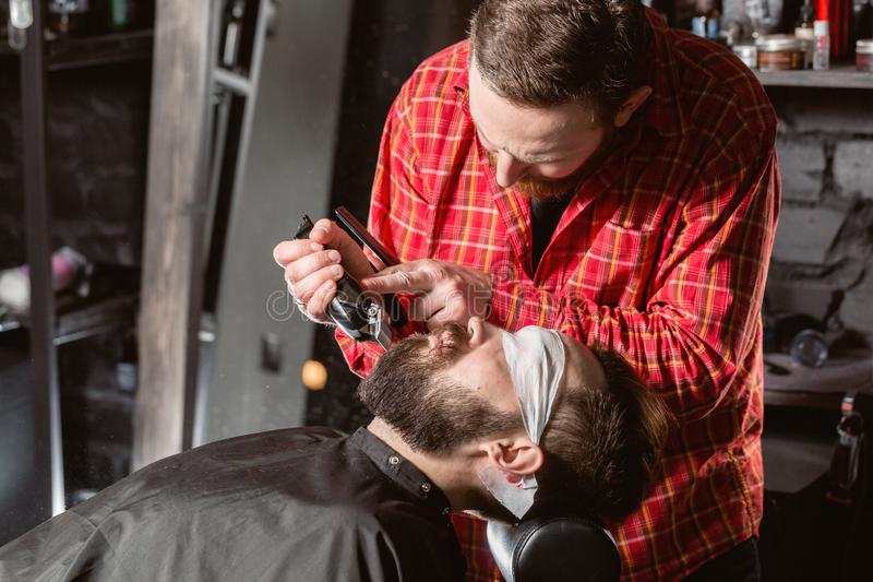 Barber work with clipper machine in barbershop. Professional trimmer tool cuts beard and hair of young guy in barber. Shop salon stock photos