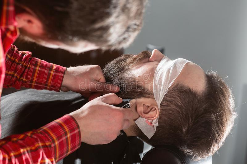 Barber work with clipper machine in barbershop. Professional trimmer tool cuts beard and hair of young guy in barber. Shop salon stock photography