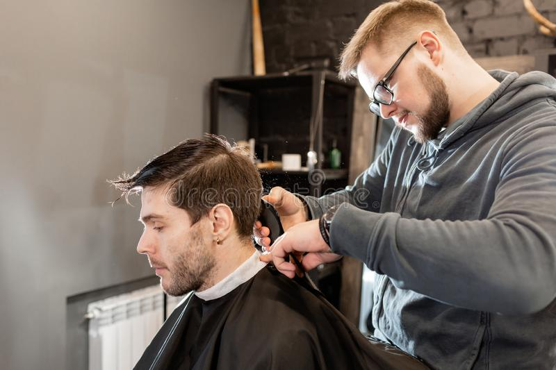 Barber work with clipper machine in barbershop. Professional trimmer tool cuts beard and hair on young guy in barber. Hair cutting with metal scissors. Master royalty free stock image