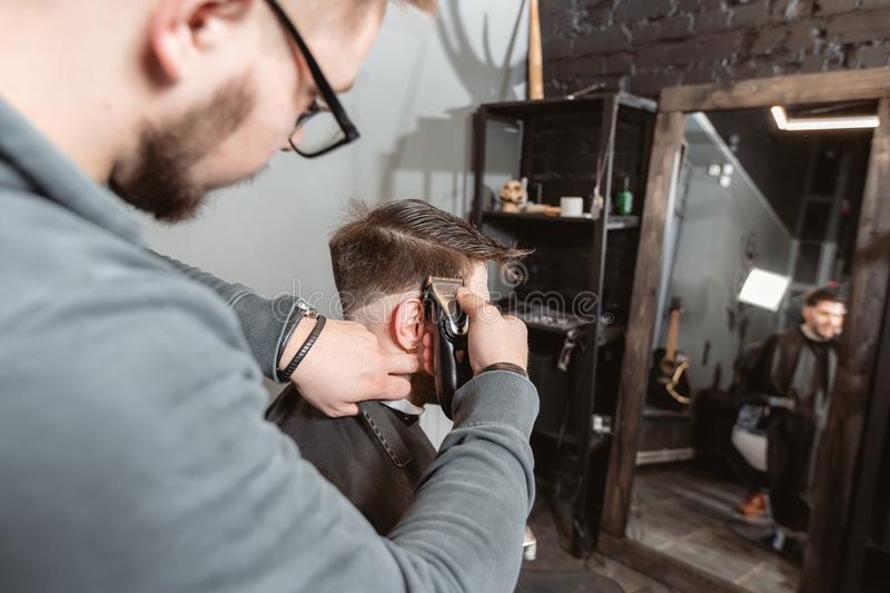 Barber work with clipper machine in barbershop. Professional trimmer tool cuts beard and hair on young guy in barber. Hair cutting with metal scissors. Master royalty free stock photo