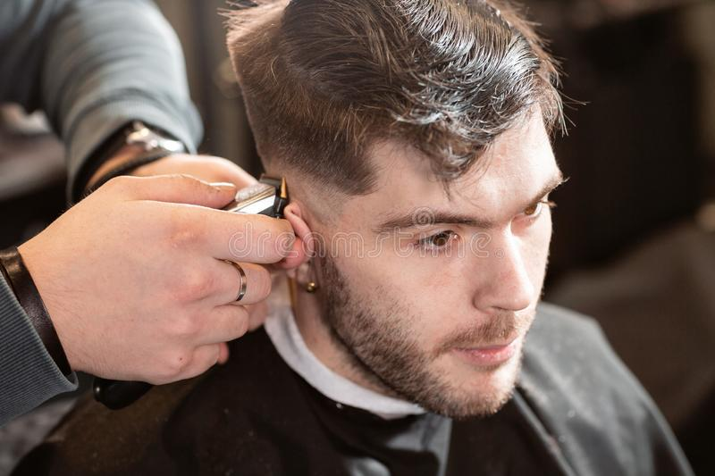 Barber work with clipper machine in barbershop. Professional trimmer tool cuts beard and hair on young guy in barber royalty free stock images