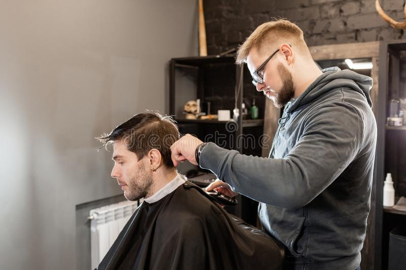 Barber work with clipper machine in barbershop. Professional trimmer tool cuts beard and hair on young guy in barber. Hair cutting with metal scissors. Master royalty free stock photos